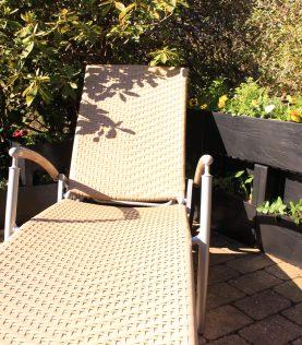 Agro Block op het terras met bloemen en een stoel.