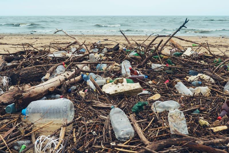 Muoviset pilaantumisastiat pullot ranta